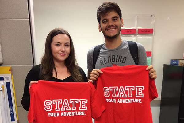 two students holding STATE your adventure shirts