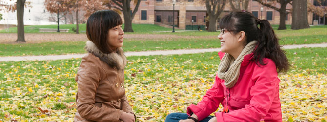 two female students sitting on the quad in fall